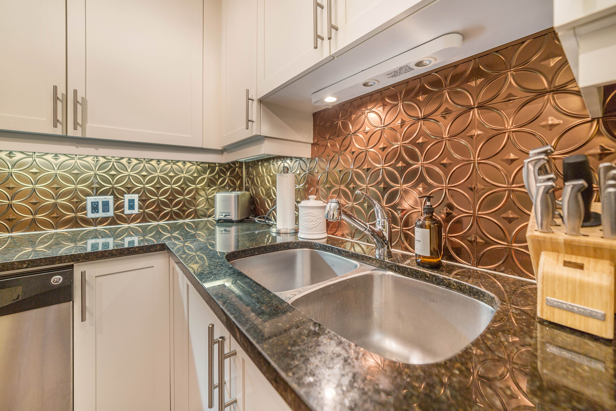 Large eat in kitchen with granite countertops, copper backsplash, and stainless steel appliances.
