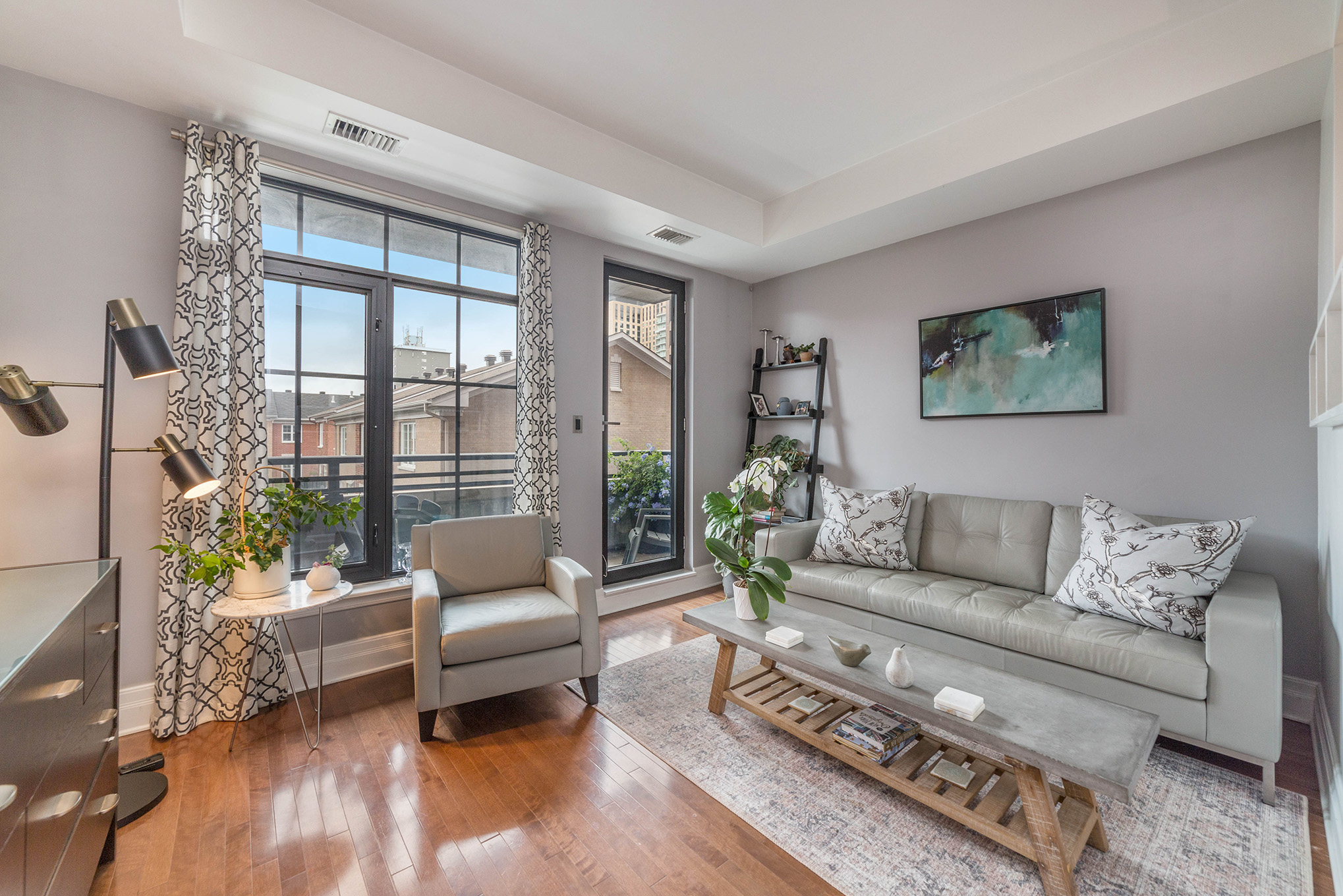 Bright living space with large windows and door heading out to a private balcony