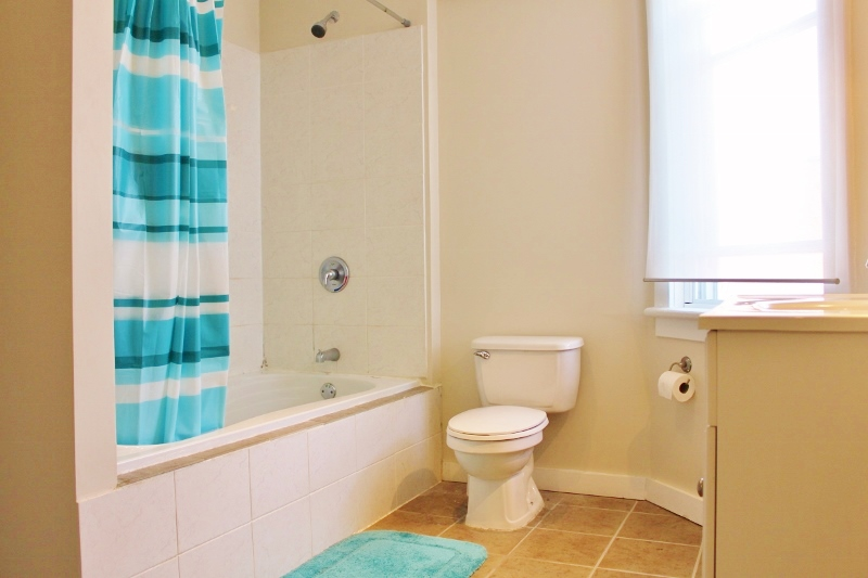 Large bathroom with ceramic tiles, deep tub, lots of storage