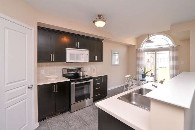 Spacious kitchen with loads of counter and cabinet space as well as a large pantry. Mostly stainless steel appliances, nice tile work, and a large eating area with floor to ceiling windows.