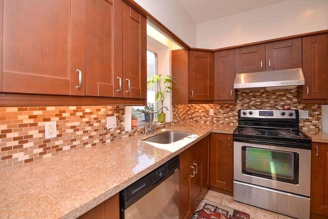 Nicely updated Kitchen with stainless steel appliances, granite counter tops, marble floors, lots of cabinet and counter space.