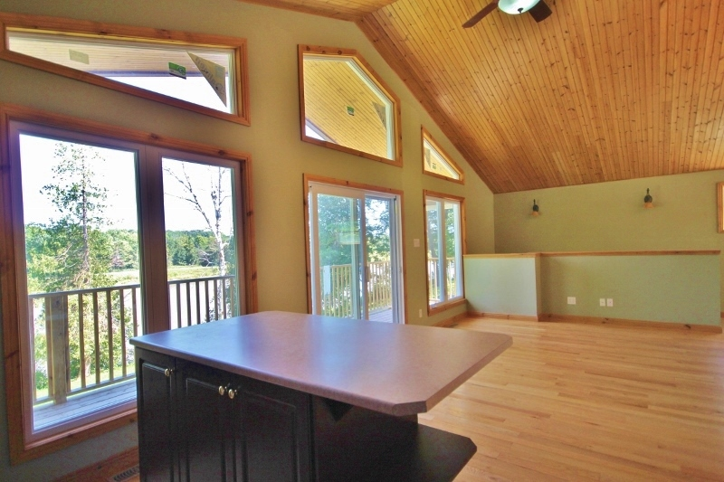 Large kitchen island with overhang, patio doors leading out to gorgeous second storey patio.