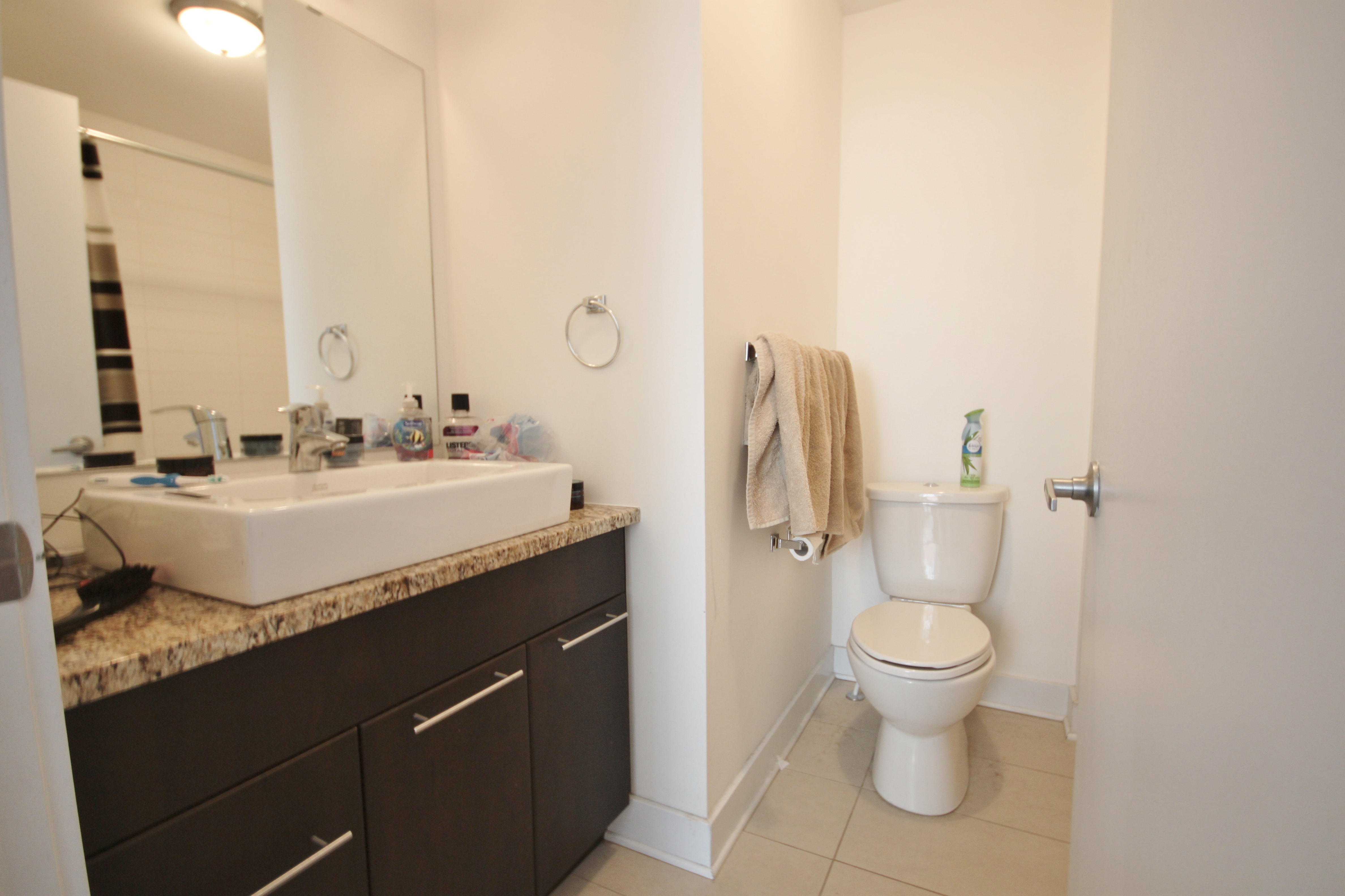 Spacious modern bathroom, with tiled flooring and shower area.