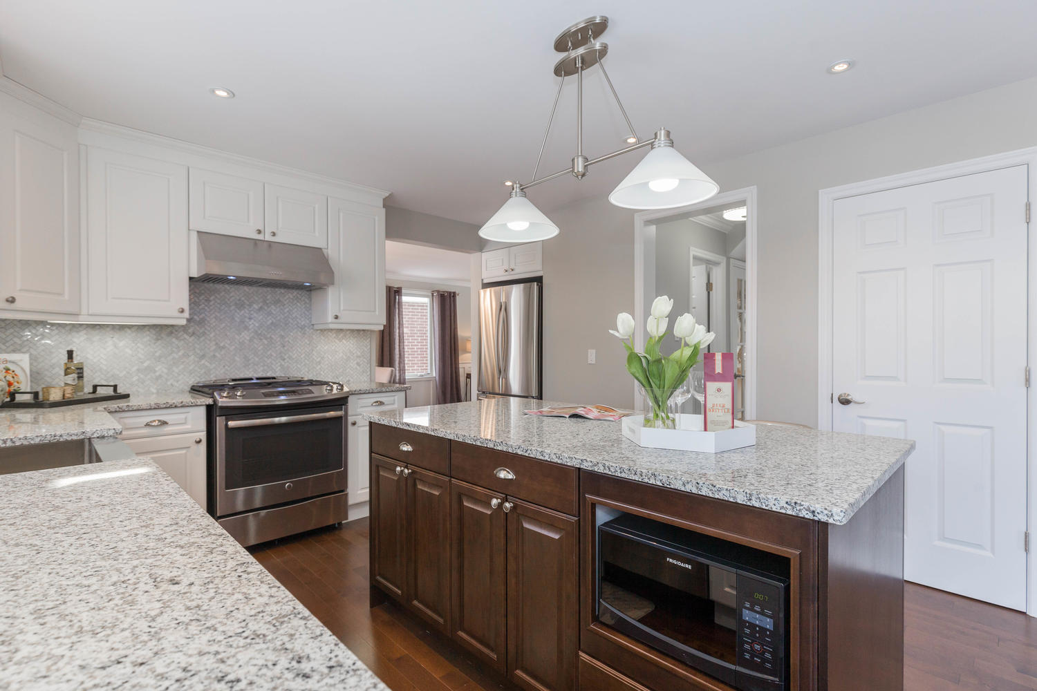 New white kitchen with granite counter top and marble back-splash, built in  pantry and centre island  > New stainless steel appliances in kitchen  > Slide in gas range with stainless steel exhaust hood