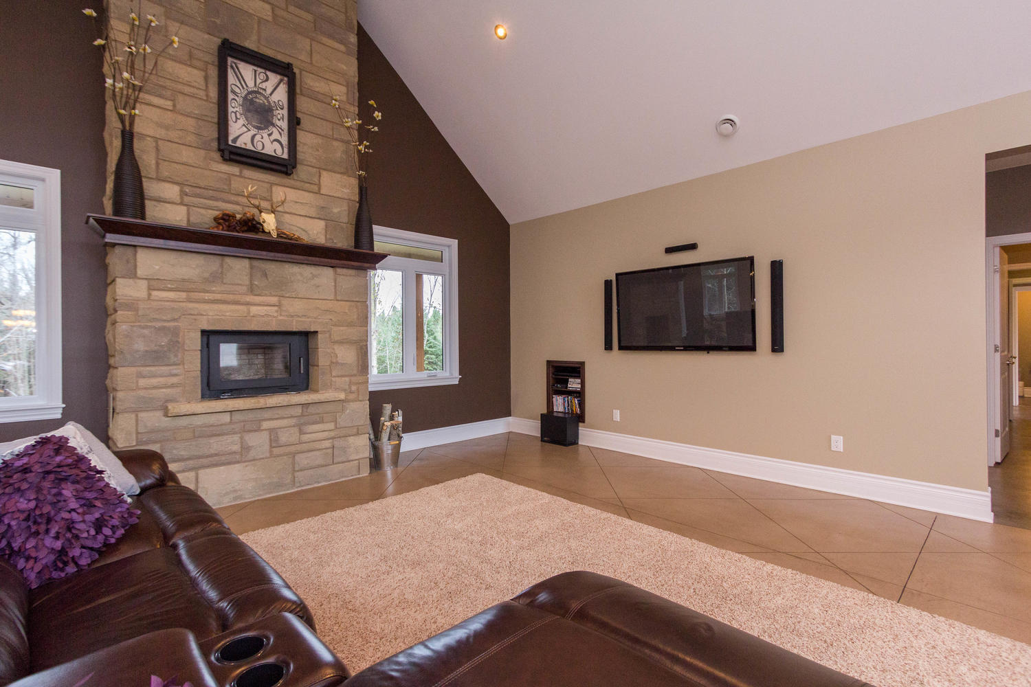 Large open living area that features a beautiful custom built stone fireplace, concrete heated flooring, flat screen TV with mount and stereo equipment included
