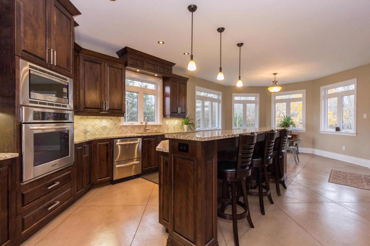 Absolutely beautiful open kitchen with granite counters, rich dark cabinetry, stainless steel appliances, huge island with breakfast bar, and a large bright eating area.