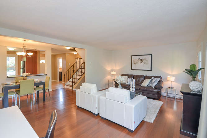 Spacious living room on main floor with exit to back patio, gleaming hardwood flooring.