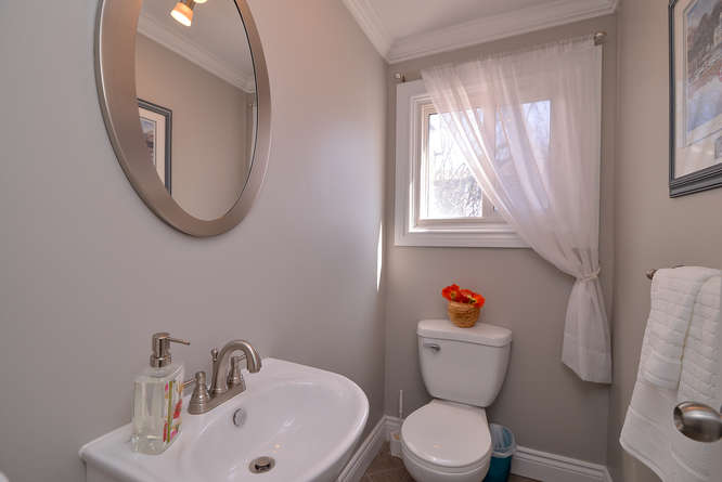 Gorgeous and bright, this powder room is conveniently located on the same level as the kitchen and dining, but just far enough away.