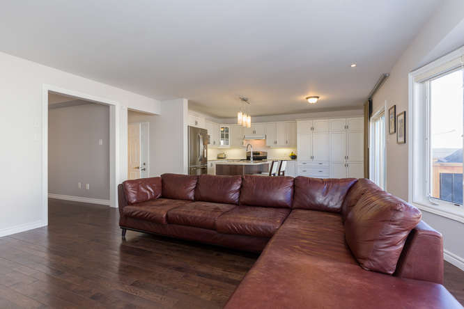 Main floor living area with gleaming hardwood flooring, loads of natural light, gas burning fireplace, open concept layout with kitchen/eating area.