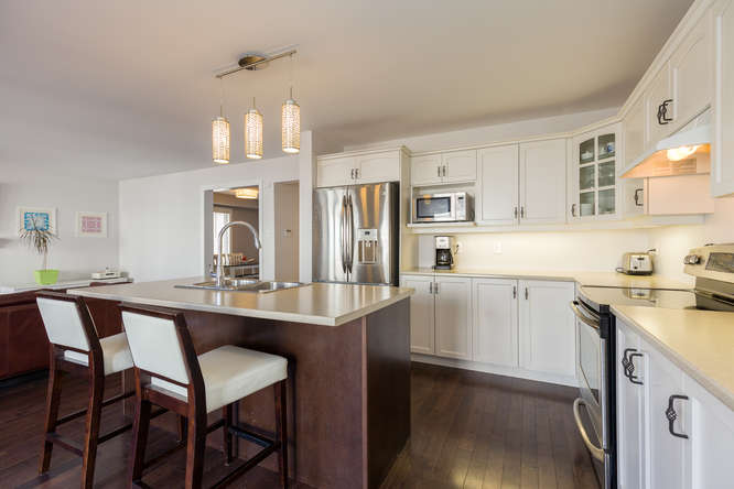 Large eatin kitchen with breakfast bar, stainless steel appliances, loads of counter space and upgraded kitchen pantry for added storage.