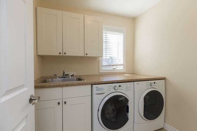 Located on the upper level, beautiful laundry room with build in cabinets, sink and counter.