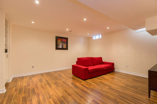 Family room on the lower level with beautiful and durable laminate flooring and built in shelving.