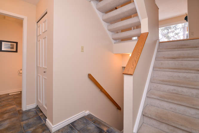 Spacious Entry way with ceramic tiles, powder room and closet, leads downstairs as well with a family room, laundry room and even more storage!