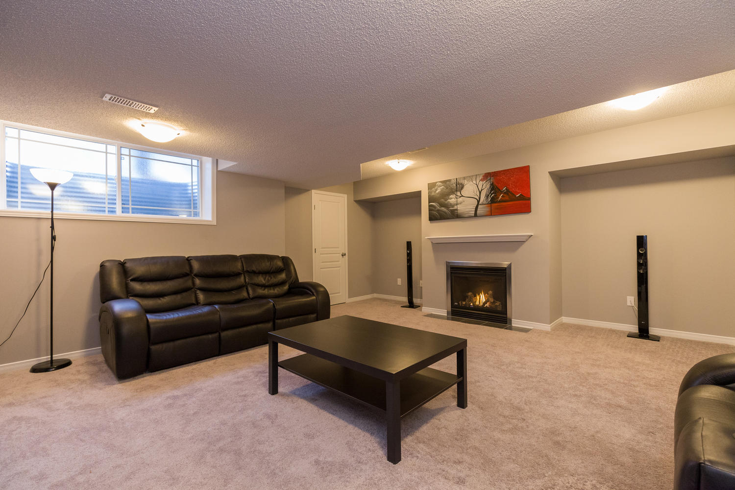 Lower level family room with comfortable plush carpeting, natural gas fireplace and lots of natural light.