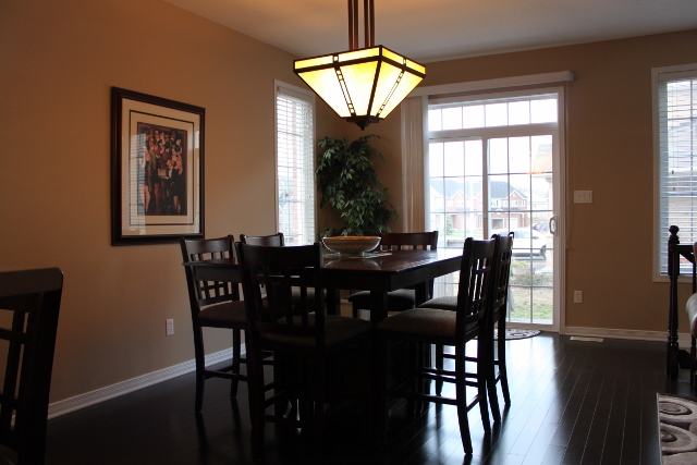 Dining room with gorgeous dark gleaming hardwood flooring and a gorgeous chandelier