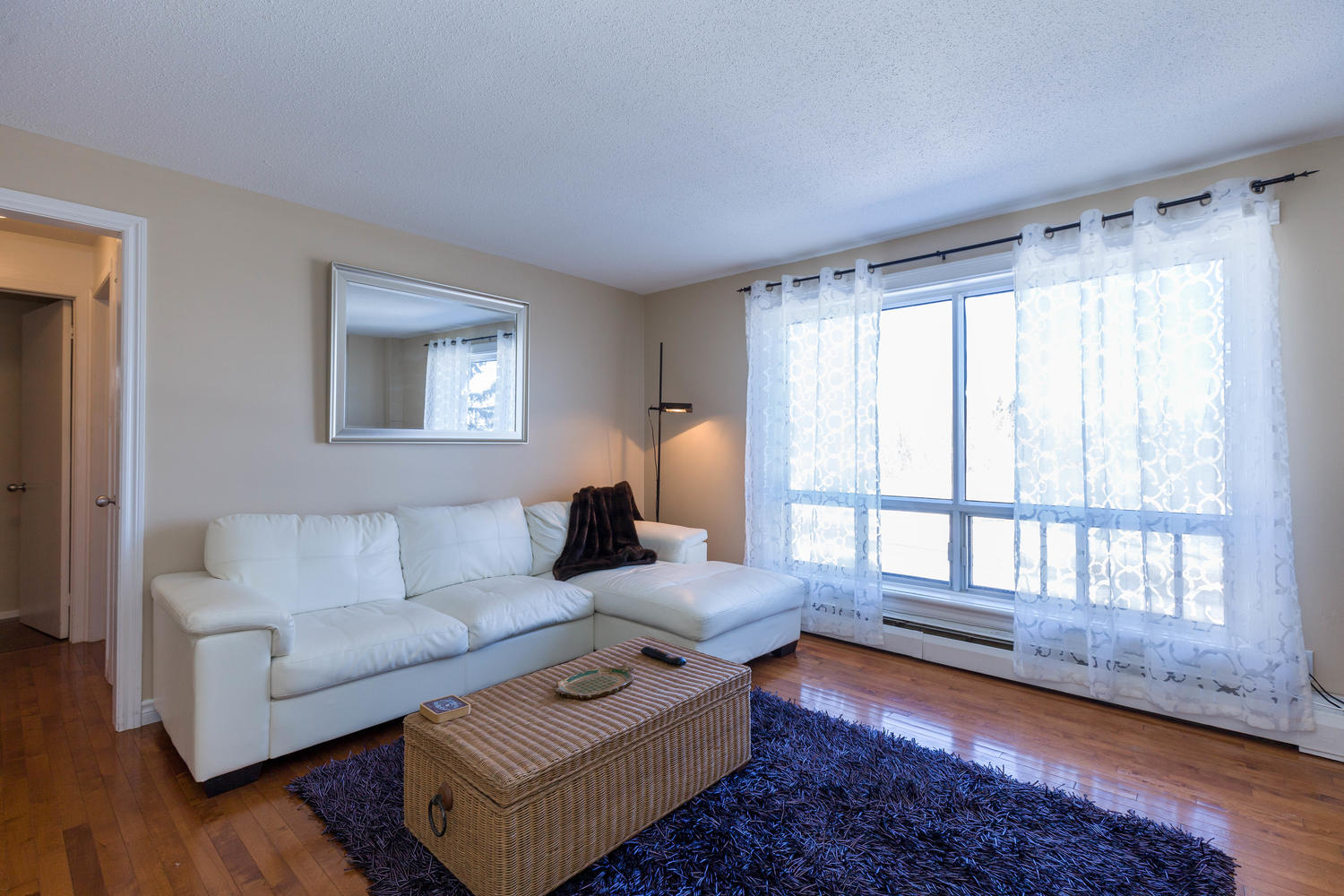 Spacious living area with hardwood flooring, large windows with great views of surrounding trees and Gatineau hills off in the distance
