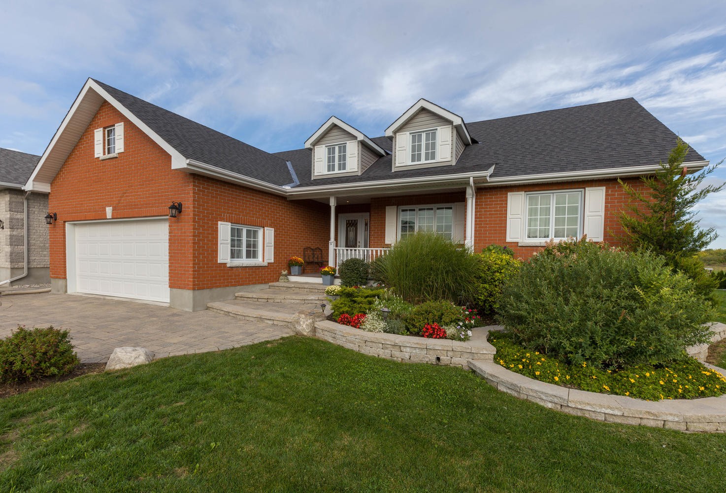 Walking up to this one just feels like home.  Interlock walk way and front steps, beautiful low maintenance landscaping surrounding it, a large front covered porch perfect for those morning coffees catching the sunrise.