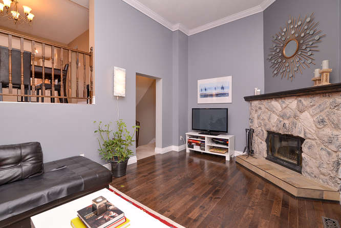 Large living space with 2 storey high ceilings, rich dark hardwood flooring and a wood burning fire place.