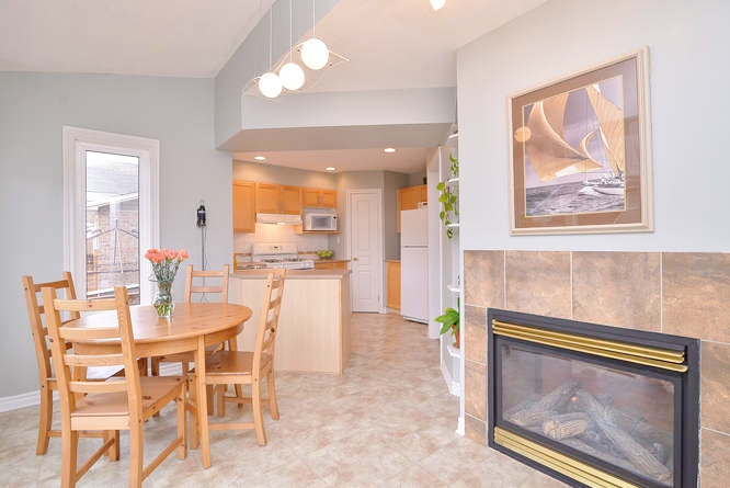 Huge eat in kitchen area with gas fireplace, loads of windows with natural light flooding the room, spacious kitchen area with island.