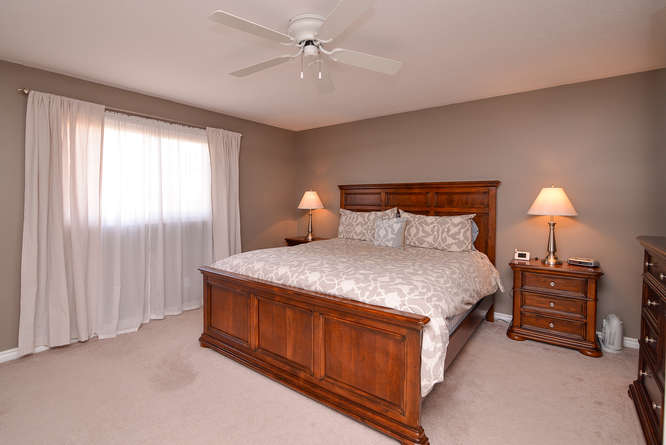 Large master bedroom with double doors, plush carpets for added comfort.