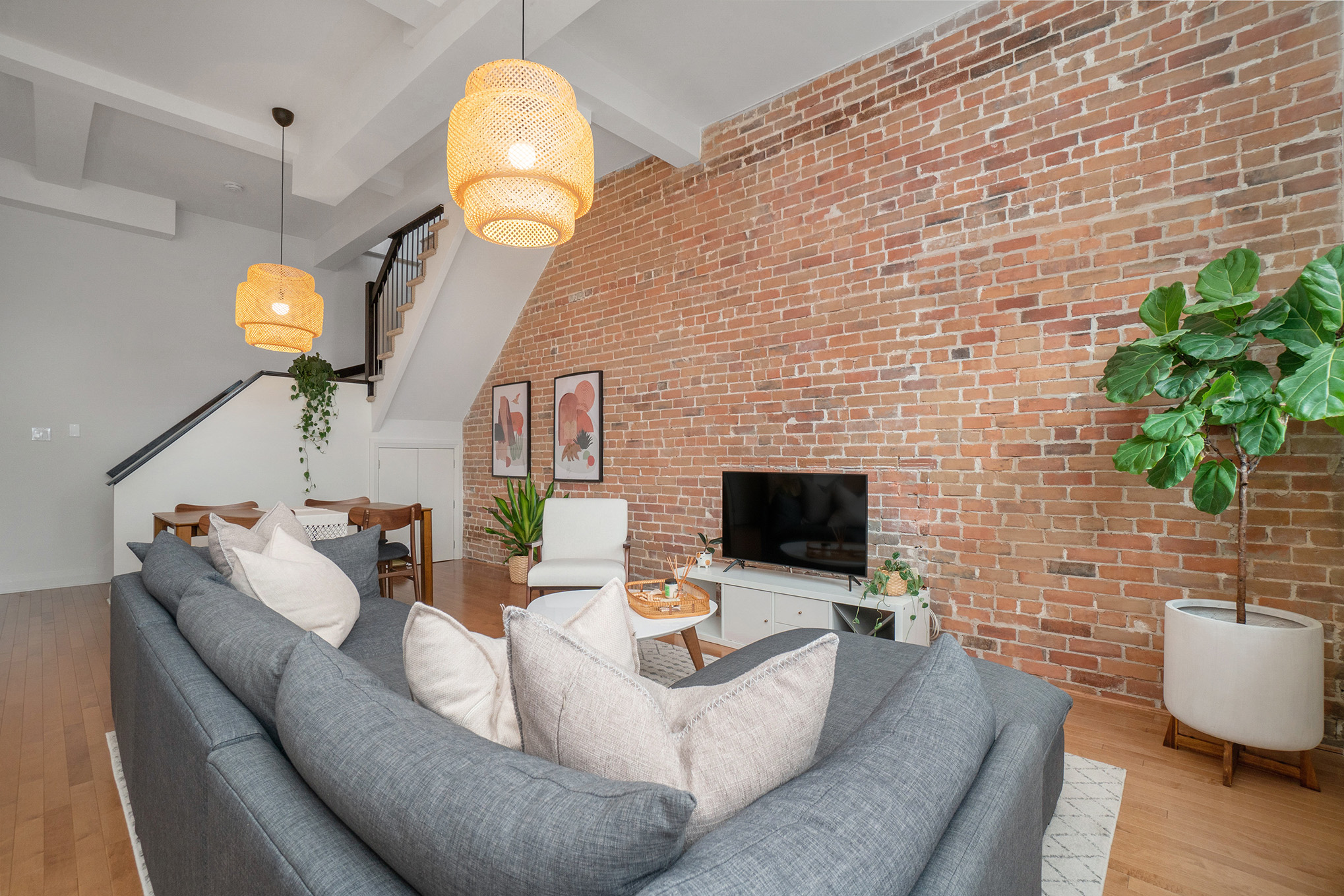 Open Concept main floor with 12ft ceilings, exposed brick wall, large kitchen with island, dining space, powder room, storage