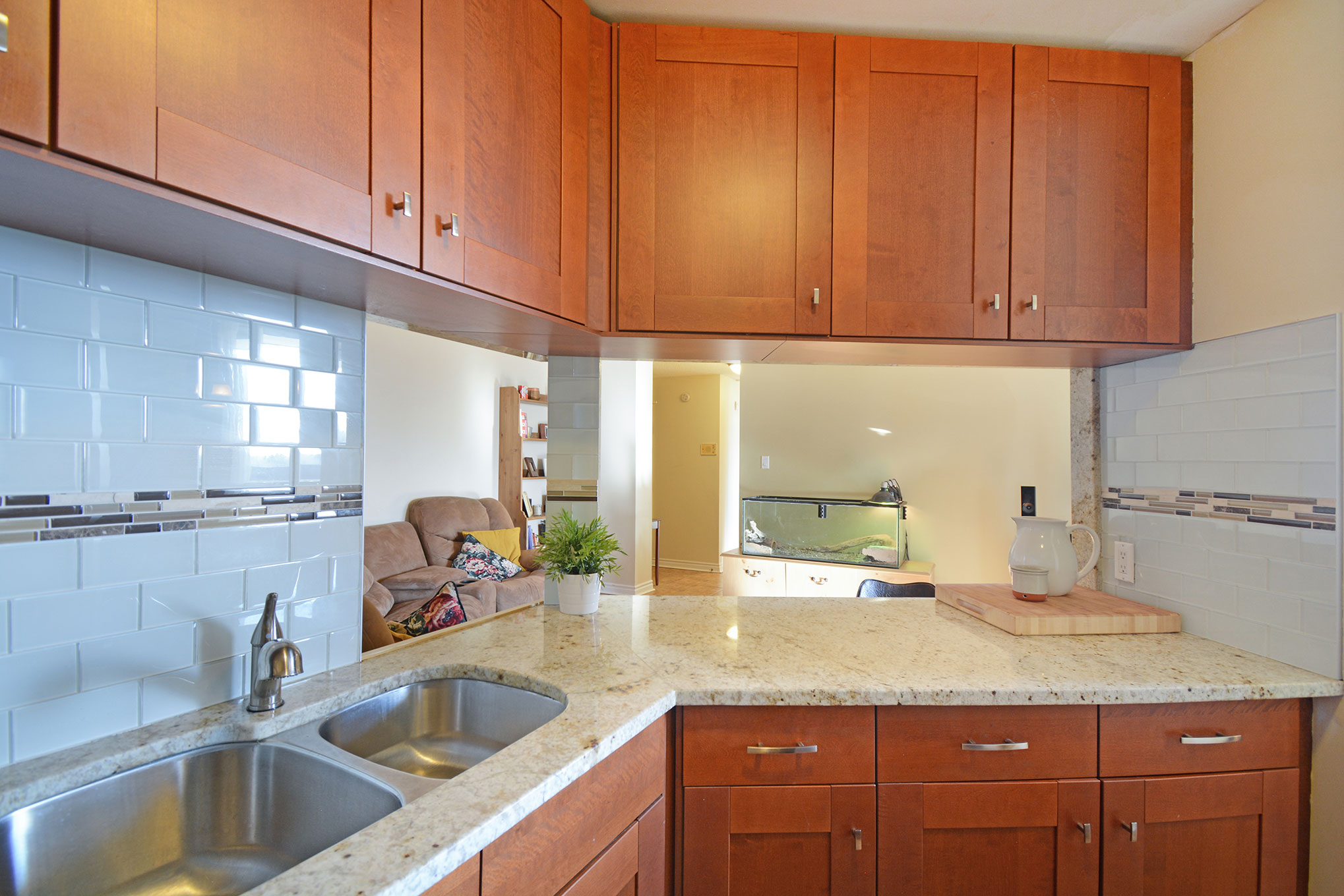 Beautiful kitchen with granite counters, tiled backsplash, stainless steel appliances and ceramic flooring.