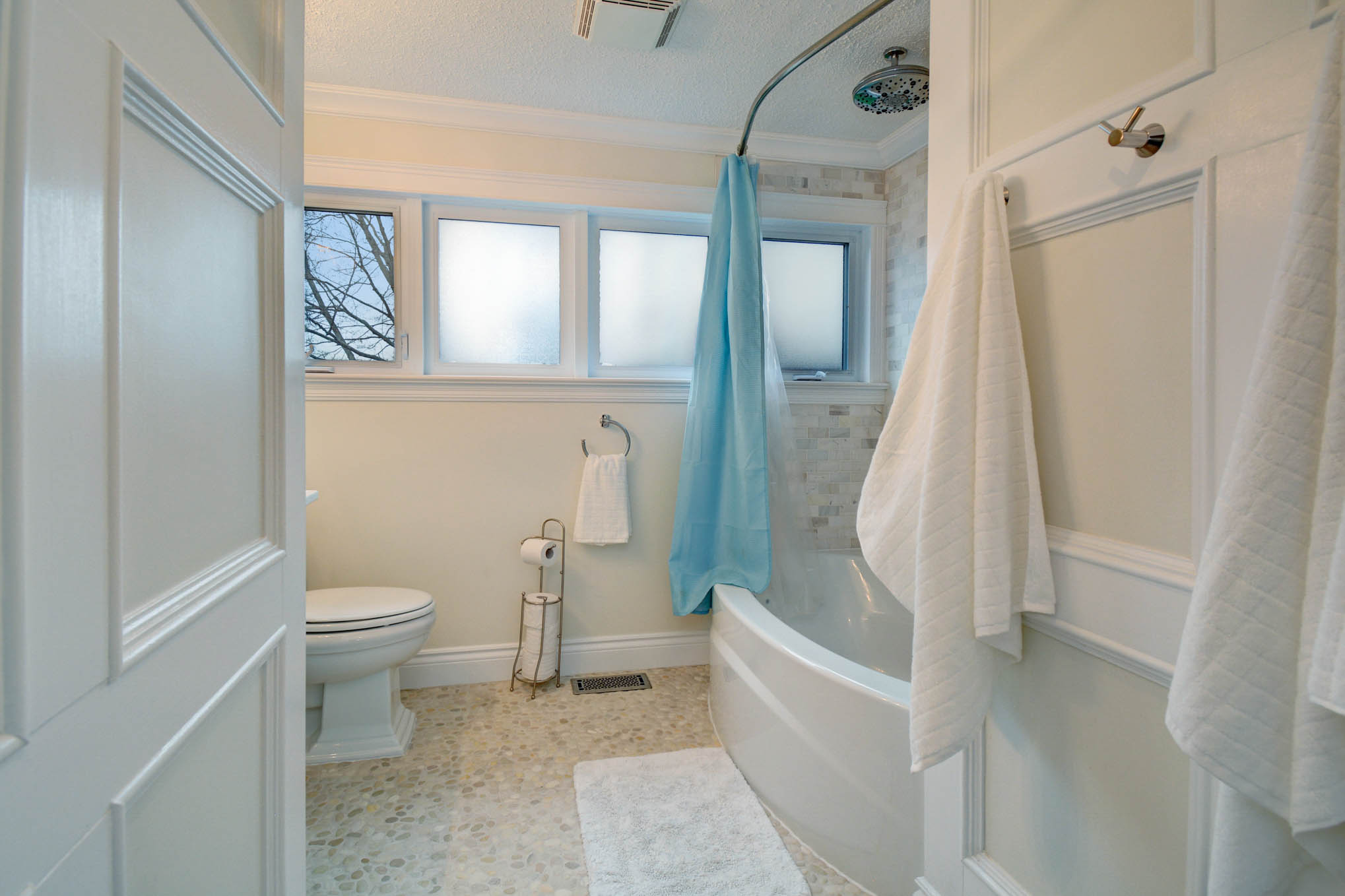 Large spa inspired full bath with custom pebble/stone flooring, and exceptional tile work, huge tub/shower combo with rainshower.