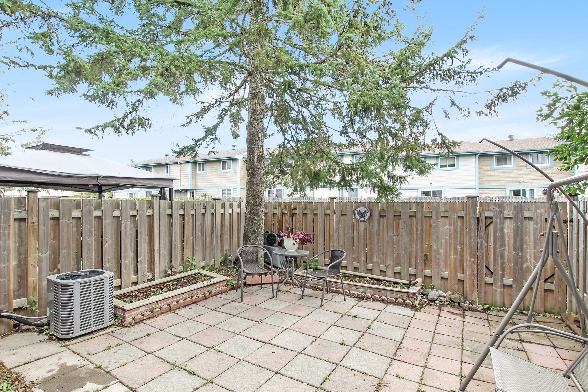 You have enough grass beside the home so no need to have to cut any in your own backyard.  This low maintenance backyard has a large private patio.