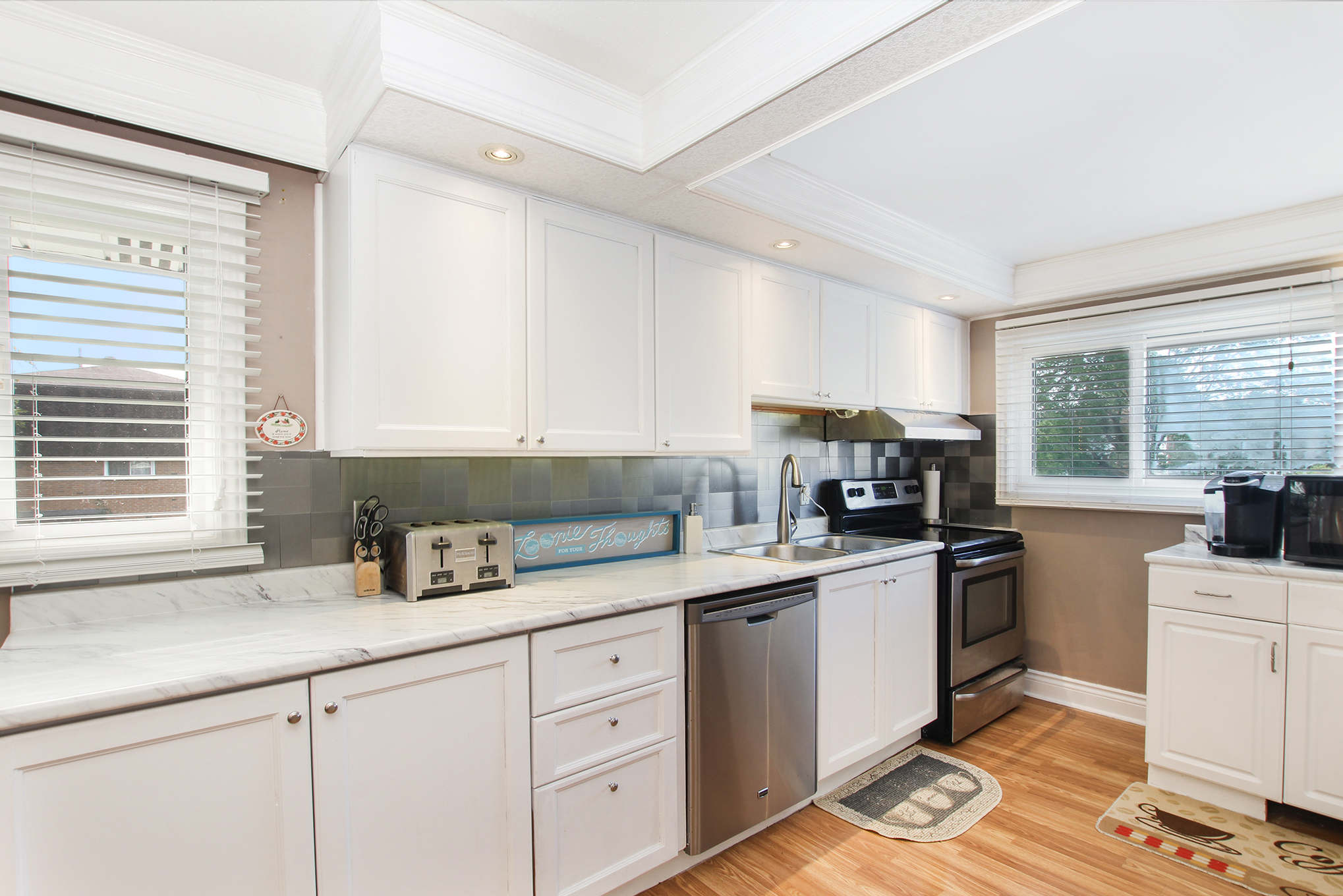 Spacious kitchen with stainless steel backsplash, stainless steel appliances, laundry area, loads of cabinet and counter space, great sized dining area overlooking living room.