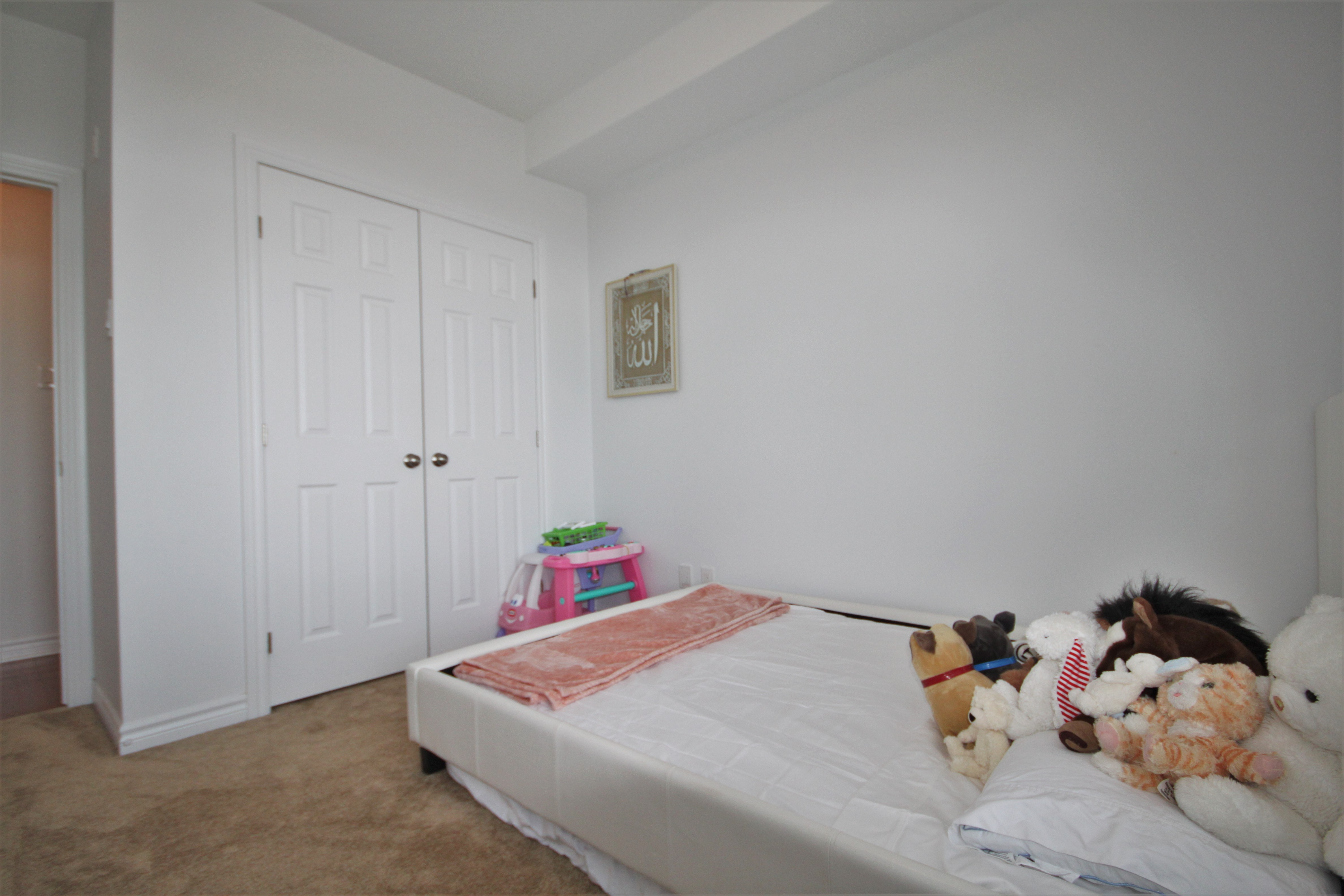 Spacious second bedroom with large closet and plush carpeting.