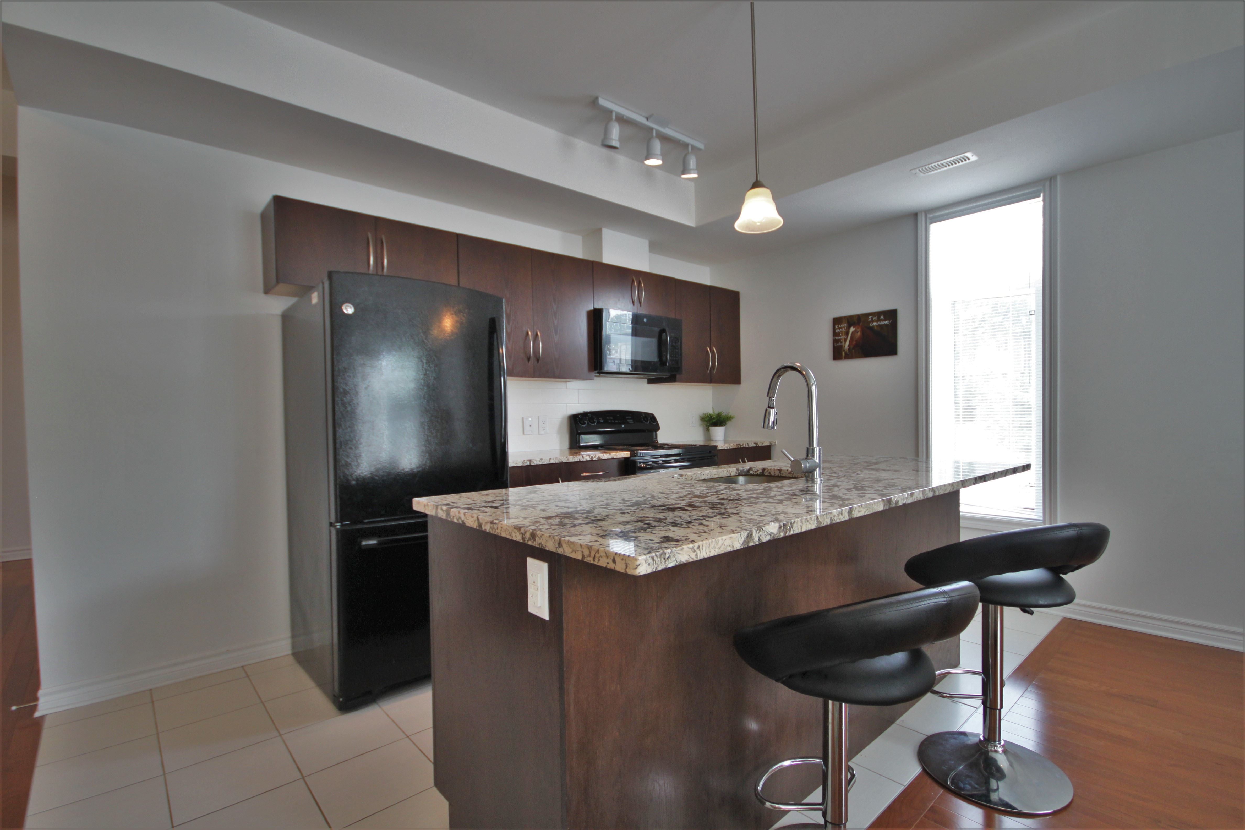 Bright & large open concept kitchen/dining/living space, with hardwood floors, huge island, granite counters, and lots of cabinet and cupboard space.