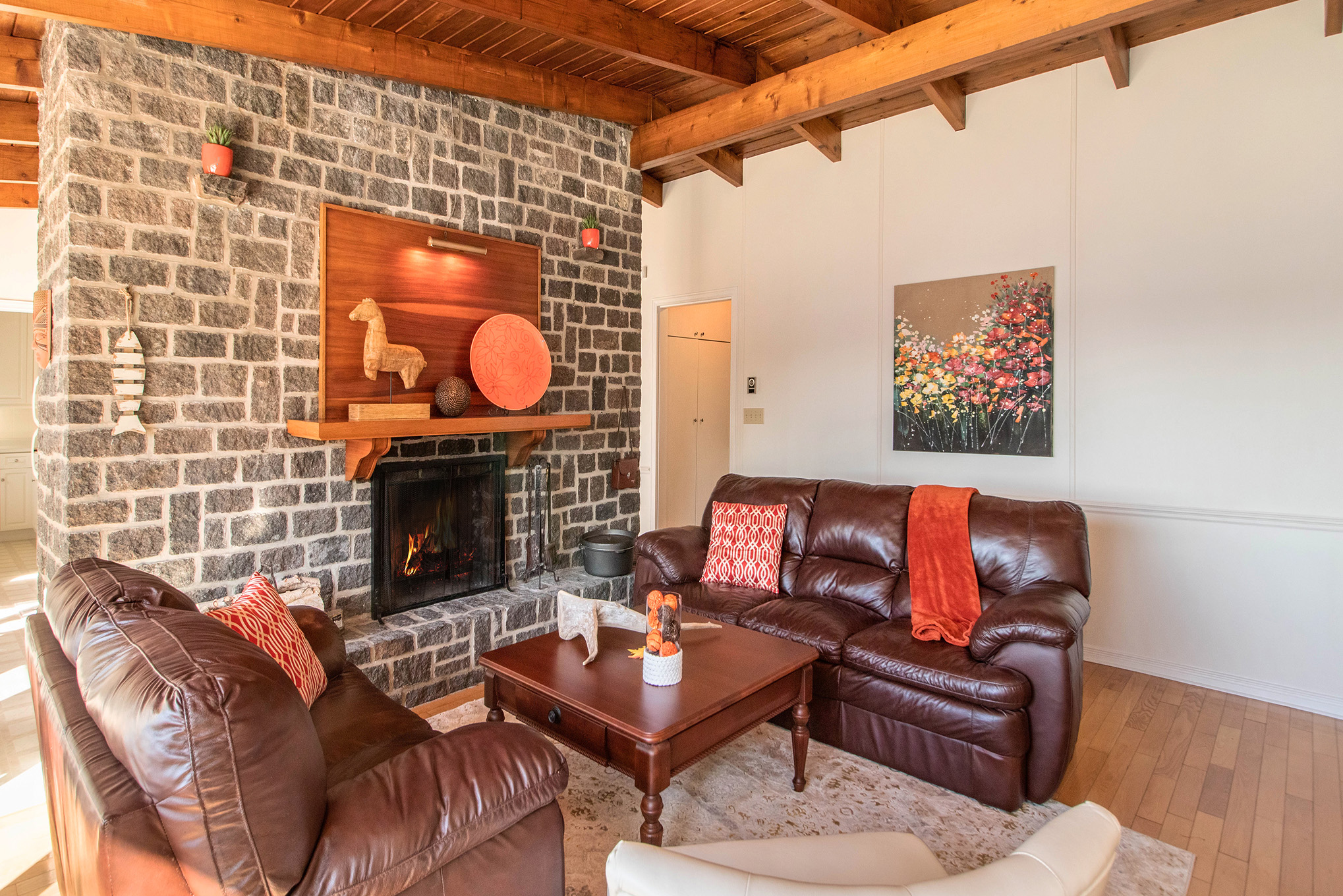 Beautiful main floor living room with stunning views and a custom wood burning fireplace, skip the kitchen, this is the heart of the home right here.
