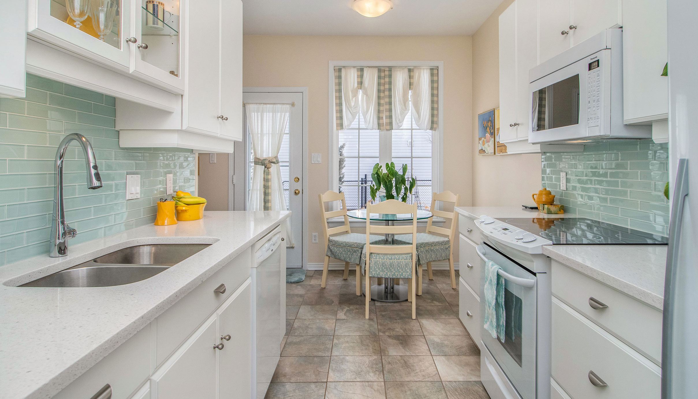 Stunning white and bright galley style kitchen with quartz counter tops and glass tiled backsplace.  Also has a nice eating area.