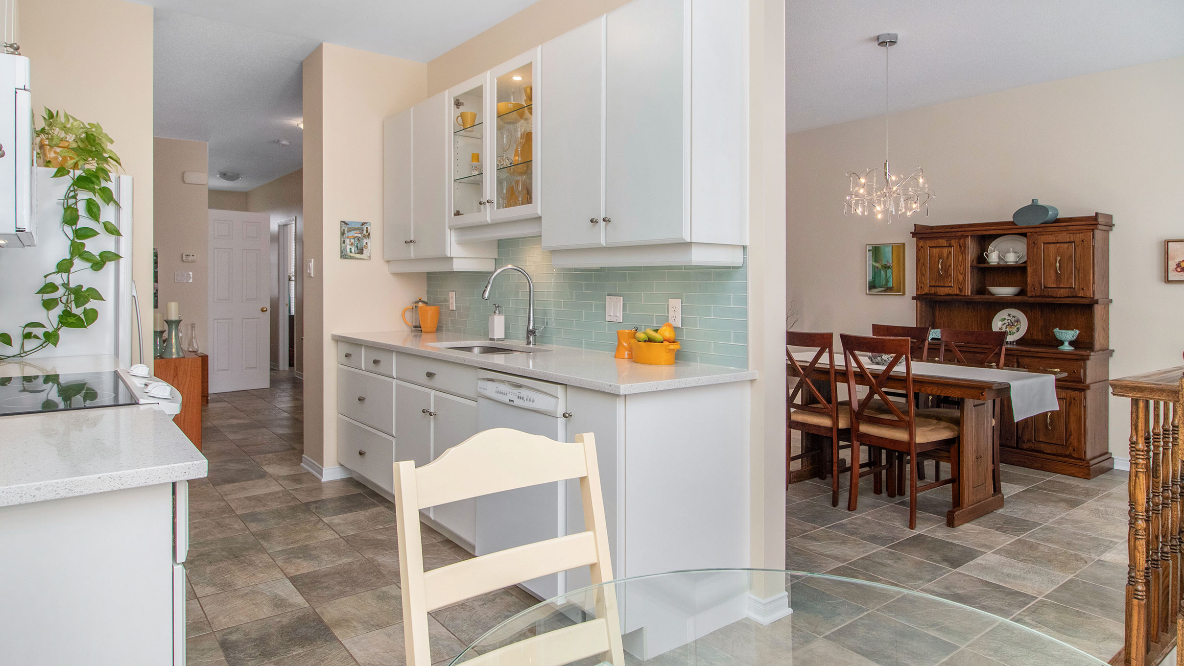 Stunning white and bright galley style kitchen with quartz counter tops and glass tiled backsplace.  Also has a nice eating area