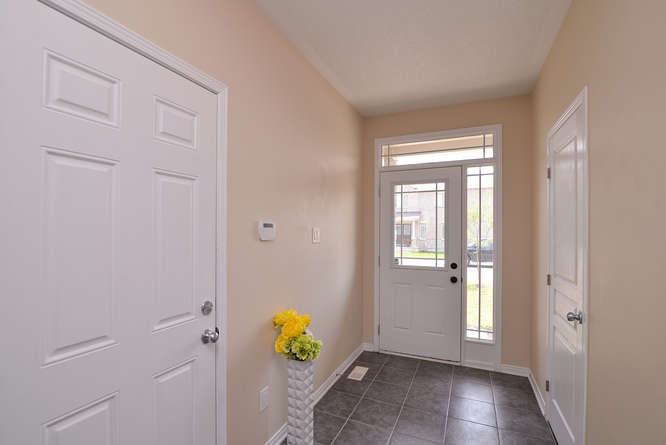Spacious tiled entry with large storage closet, access to garage and powder room