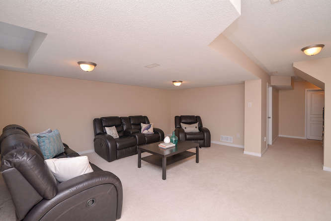 Large finished family room with plush carpets, natural gas fireplace, and a bathroom roughed in.